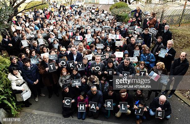 French residents hold signs reading 'Je suis Charlie' to pay tribute to the victims of the Charlie Hebdo attack that killed 12 people on January 7...