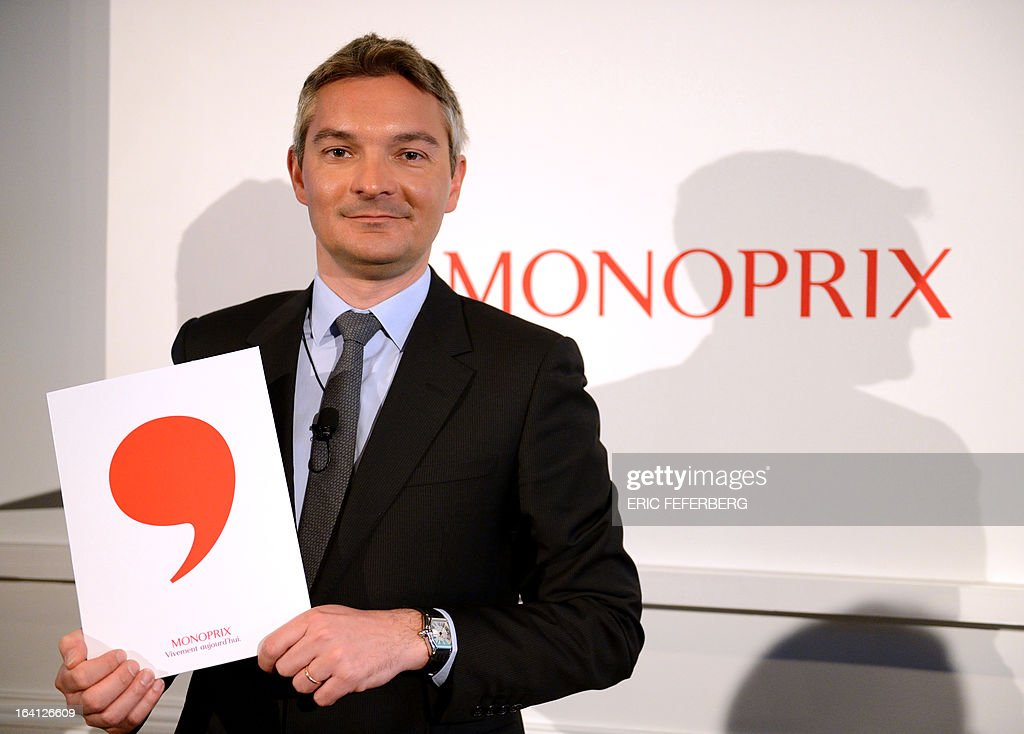 French retail chain Monoprix General Director Stephane Maquaire poses in front of the shops' new logo on March 20, 2013 during a press conference sin Paris.