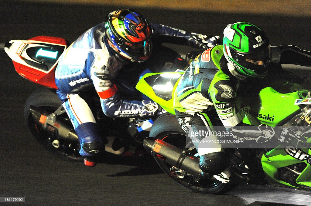French rider Fabien Foret (R) on his Kawasaki ZX10 N°11 competes ahead of French pilot Alexander Cudlin (L) on his Suzuki GSXR 1000 N°1 during the night practice session of the Le Mans 24-Hour endurance moto race on September 19, 2013, in Le Mans, western France. 168 riders on 56 motorcycles will take part in the 36th 24 Hours of Le Mans, on September 21, 2013. AFP PHOTO / JEAN-FRANCOIS MONIER