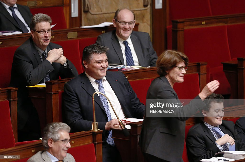 French right wing UMP party MP David Douillet (C) reacts as Junior Minister for the Elderly and Disabled, Michele Delaunay (2ndR) speaks during the debate on legalising same-sex marriage at the National Assembly on February 7, 2013 in Paris. France's Parliament began examining draft legislation on same-sex marriage after months of rancorous debate and huge street protests by both supporters and opponents. The proposed law still faces at least another week of scrutiny before a final vote scheduled for February 12, it now looks set to emerge from parliament without delay and undiluted.