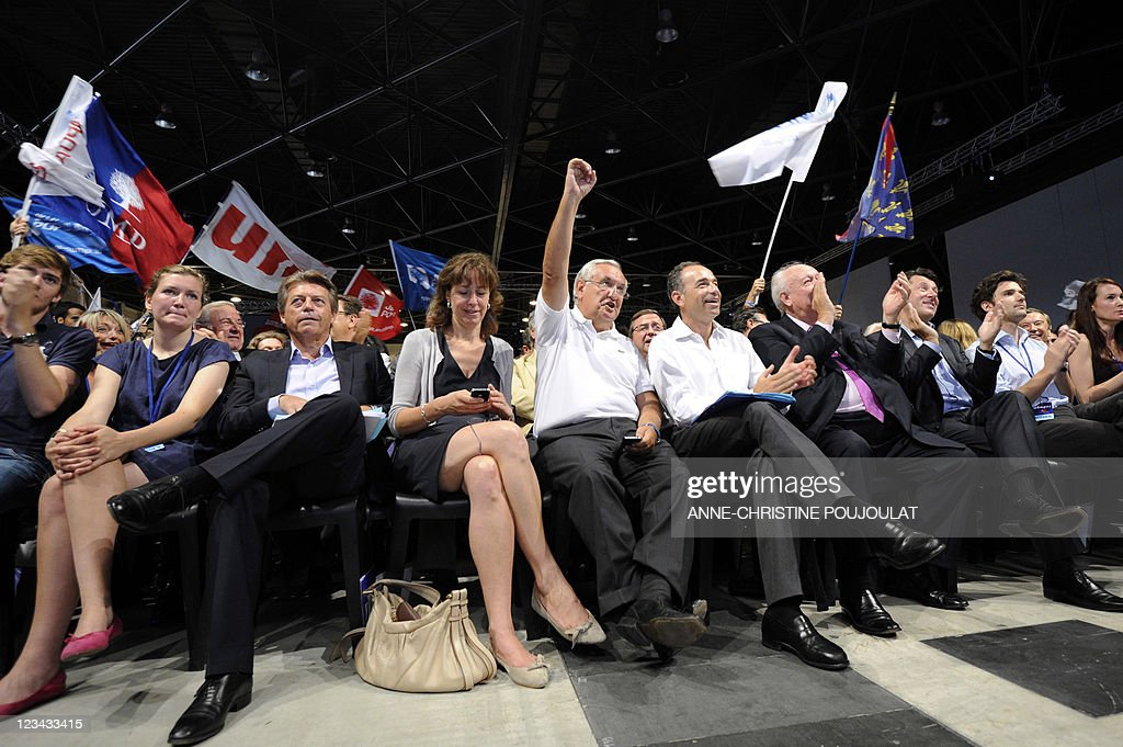 French right wing UMP party vice president national council Jean-Pierre Raffarin (C) holds an arm, flanked by UMP Bas-Rhin senator Fabienne Keller, UMP general secretary Jean-François Copé and UMP Senator Mayor Jean-Claude Gaudin, during the French right wing UMP party Campus des Jeunes Populaires 2011 (Youth Popular Campus), on September 3, 2011 in Marseille, southern France.