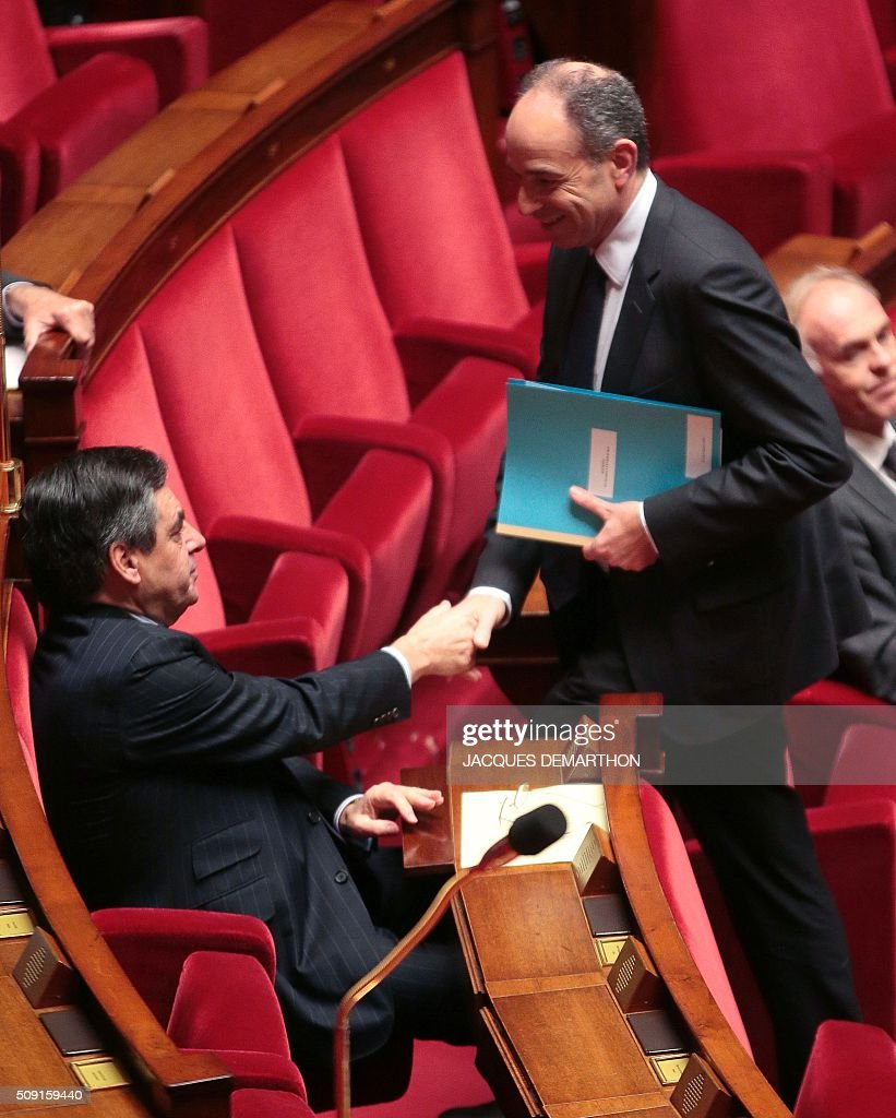 French right-wing Les Republicains (LR) MP Jean-Francois Cope (R) shakes hands with former French prime minister and LR MP Francois Fillon during a session of questions to the government at the French National Assembly in Paris on February 9, 2016. / AFP / JACQUES DEMARTHON