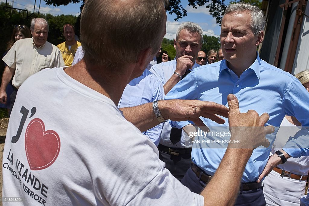 French right-wing Les Republicains (LR) party MP and candidate for the party's primary for the 2017 presidential elections, Bruno Le Maire, listens to a farmer as he pays a visit to farmers and producers of Charolais cattle, in Vendenesse-les-Charolles on June 30, 2016. / AFP / JEAN