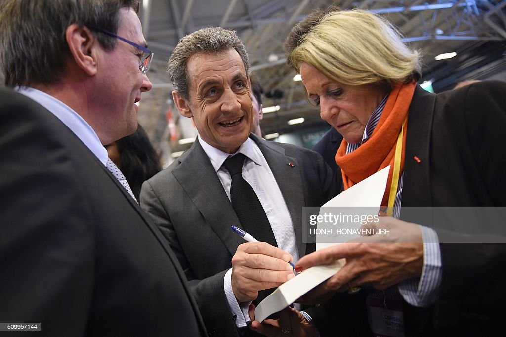 French right-wing Les Republicains (LR) party President, Nicolas Sarkozy signs a copy of his latest book during the LR National Council on February 13, 2016 in Paris. AFP PHOTO / LIONEL BONAVENTURE / AFP / LIONEL BONAVENTURE