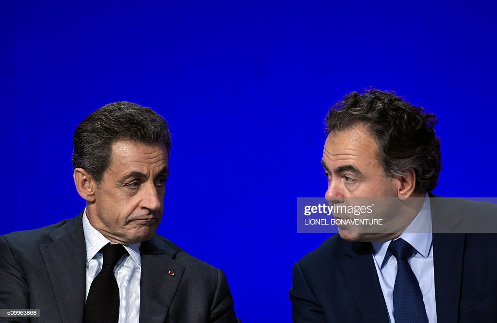 French right-wing Les Republicains (LR) party President, Nicolas Sarkozy (L) and President of the LR National Consil Luc Chatel (R) talk as they look on during the LR National Council on February 13, 2016 in Paris. AFP PHOTO / LIONEL BONAVENTURE / AFP / LIONEL BONAVENTURE
