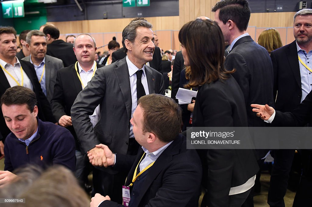 French right-wing Les Republicains (LR) party President, Nicolas Sarkozy (C) shakes hands with a unidentified man during the LR National Council on February 13, 2016 in Paris. AFP PHOTO / LIONEL BONAVENTURE / AFP / LIONEL BONAVENTURE