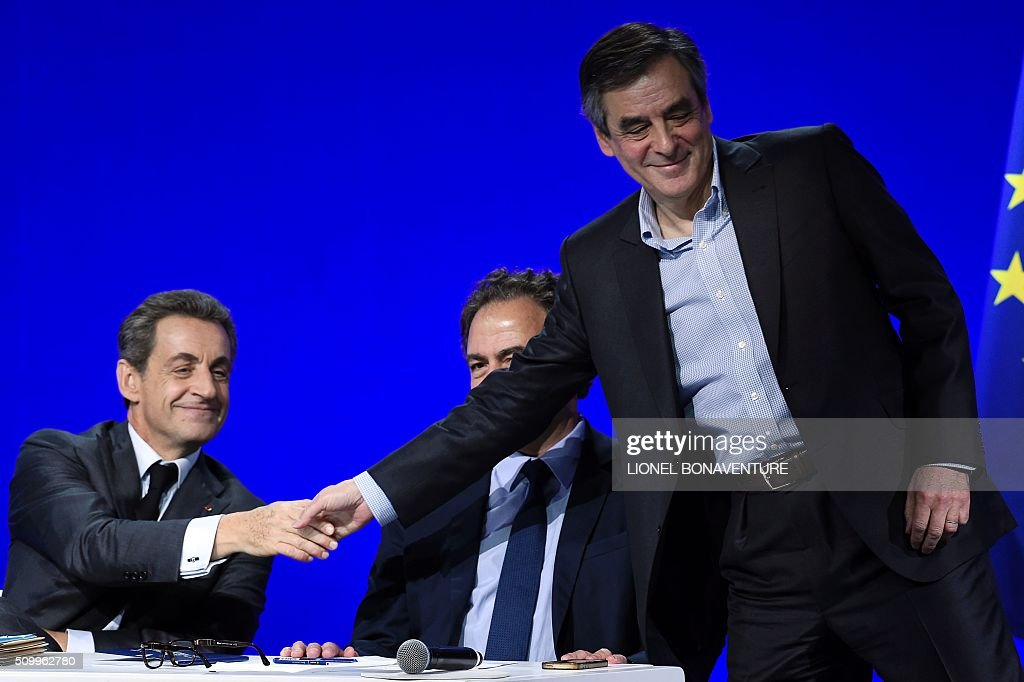 French right-wing Les Republicains (LR) party President, Nicolas Sarkozy (L) shakes hand with Former French Prime Minister and right-wing Les Republicains (LR) parliament member Francois Fillon (R) during the LR National Council on February 13, 2016 in Paris. AFP PHOTO / LIONEL BONAVENTURE / AFP / LIONEL BONAVENTURE