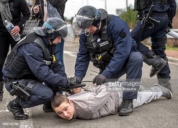 French riot police arrest a supporter of the Pegida movement during a banned demonstration in Calais northern France on February 6 2016 Around 20...