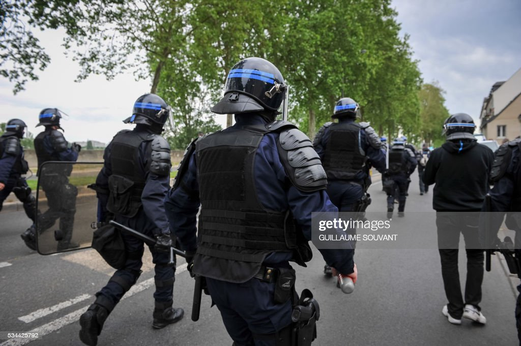 French riot police forces run during a protest against the government's planned labour law reforms on May 26, 2016 in Tours, Central France. The French government's labour market proposals, which are designed to make it easier for companies to hire and fire, have sparked a series of nationwide protests and strikes over the past three months. / AFP / GUILLAUME