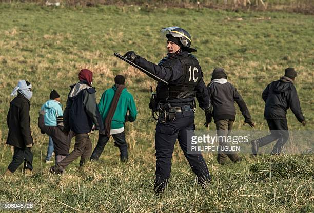 French riot police officer gestures next to migrants near the A16 motorway near the site of the Eurotunnel in Coquelles near Calais northern France...