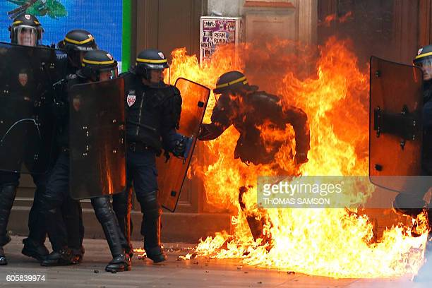 French riot police officer is surrounded by flames during a demonstration against the controversial labour reforms of the French government in Paris...