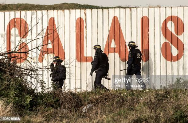 TOPSHOT French riot police officer walk in front of a fence with the lettering 'Calais' near the A16 motorway near the site of the Eurotunnel in...