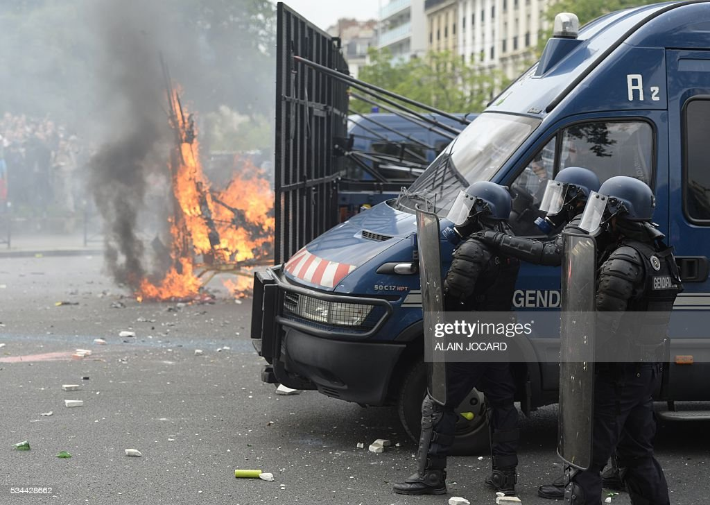 French riot police officers stand guard next to a burning barricade, during a protest against the government's labour market reforms in Paris, on May 26, 2016. The French government's labour market proposals, which are designed to make it easier for companies to hire and fire, have sparked a series of nationwide protests and strikes over the past three months.