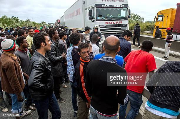 French riot police officers stand on the side of the road as illegal migrants wait to attempt to hide in lorries heading for England in the French...