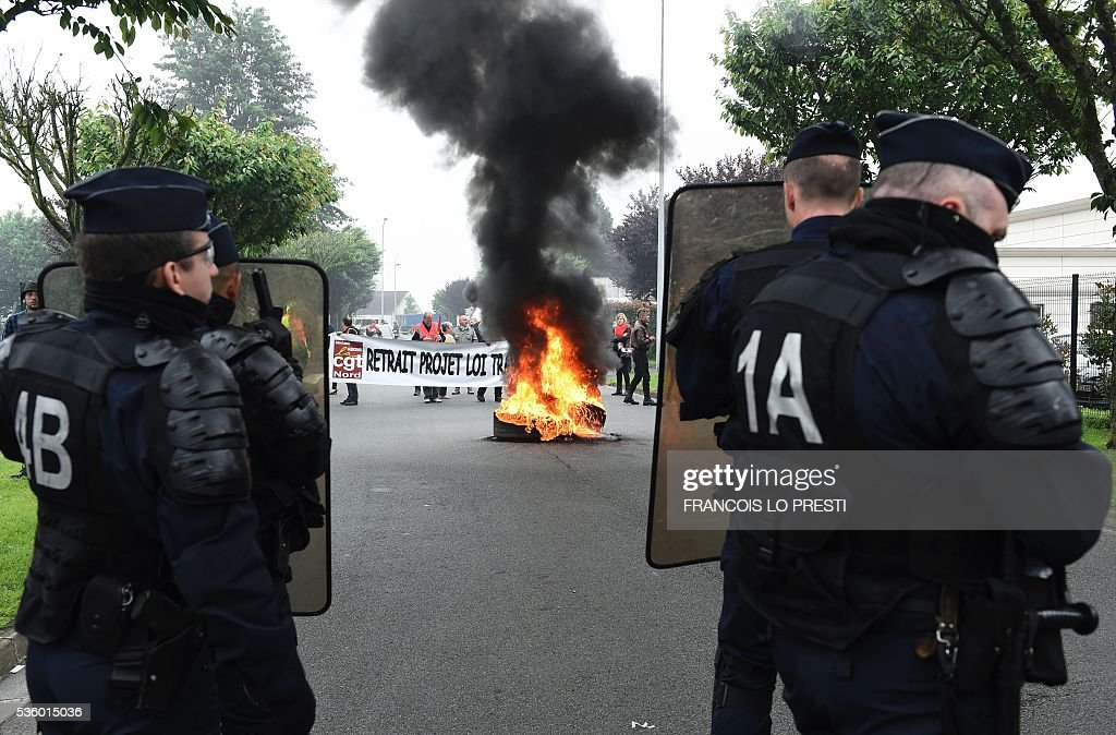 French riot police stand in front of French CGT union's members next to tires on fire during a protest against the government's planned labour law reforms at the Simmons factory in Saint Amand les Eaux, northern France on May 31, 2016 during a visit of the French Economy Minister. / AFP / FRANCOIS