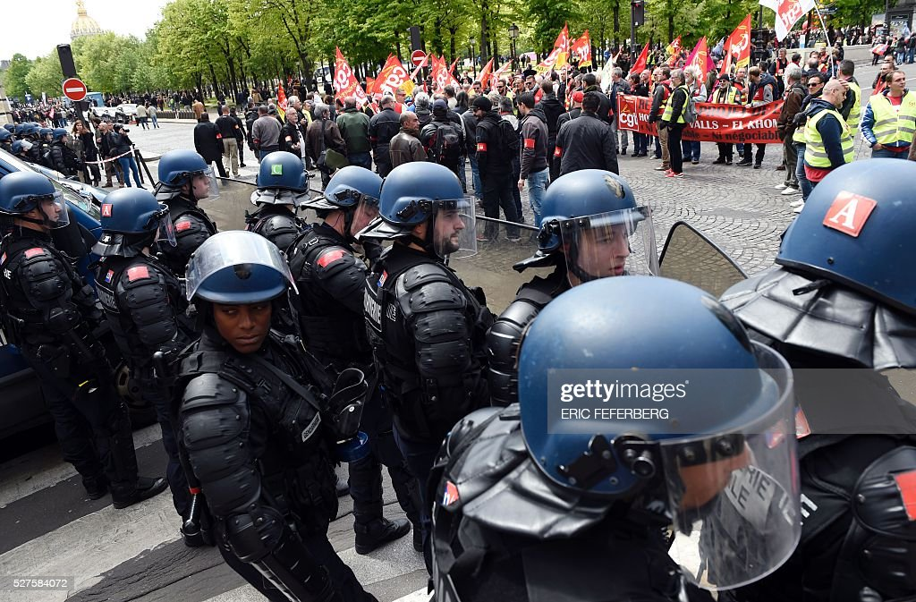 French riot police stand in front of protesters during a demonstration against the government's planned labour law reforms on May 3, 2016, in Paris as French lawmakers begin to examine the contested labour reform bill at the Parliament. Unions fear it will erode the cherished rights of workers on full-time contracts, while student organisations -- who have been at the forefront of the protests -- believe it will fail to create 'real' jobs for young people.