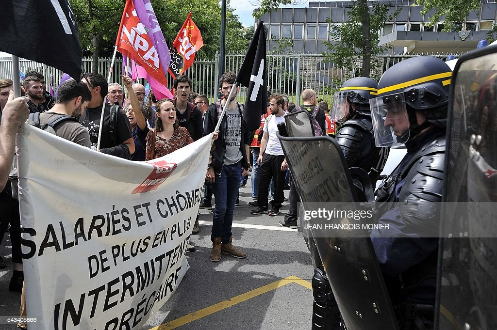 French riot police stand in front of protestors blocking a street during a demonstration against the French controversial labour reforms on June 28, 2016 in Rennes. Unions have called repeated strikes and marches in opposition to the law, which seeks to bring down France's intractable 10-percent unemployment rate by making it easier to hire and fire workers. / AFP / JEAN