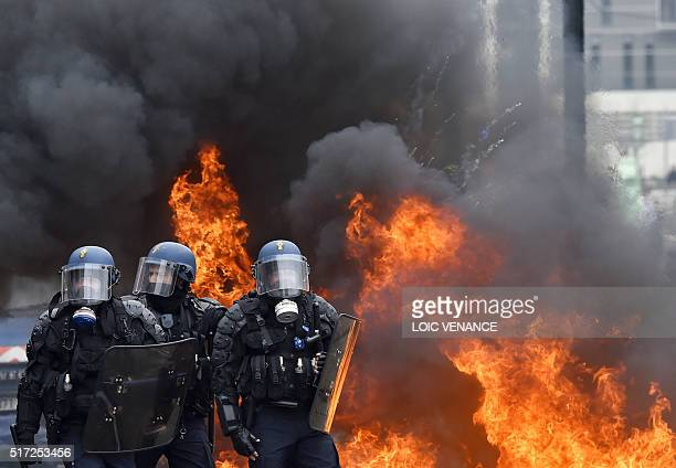 TOPSHOT French riot police stand next to a fire as they take a position after clashes erupted on March 24 2016 in Nantes western France during a...