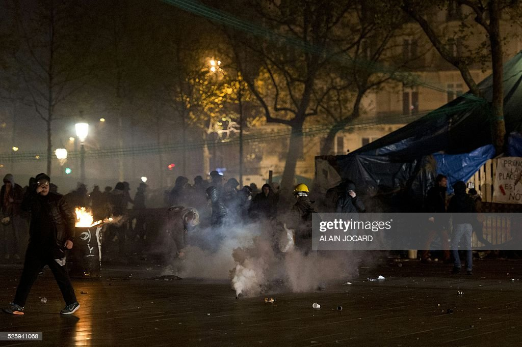 French riot police use tear gas to clear the Place de la Republique in Paris during a protest by the Nuit Debout, or 'Up All Night' movement who have been rallying against the French government's proposed labour reforms on April 29, 2016. People were arrested and others detained during the overnight clashes in the French capital as the police dispersed the protesters whose movement began on March 31 in opposition to the government's proposed labour reforms. / AFP / ALAIN