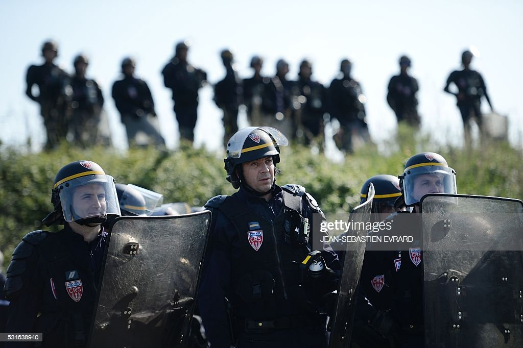 French riot policemen stand during the evacuation of workers on strike blocking the access to an oil depot near the Total refinery of Donges, western France, on May 27, 2016 to protest against the government's planned labour law reforms. The French government's labour market proposals, which are designed to make it easier for companies to hire and fire, have sparked a series of nationwide protests and strikes over the past three months. French unions on May 27 called on workers to 'continue and step up their action', as a wave of strikes against a disputed labour law disrupted transport and fuel supplies. / AFP / JEAN