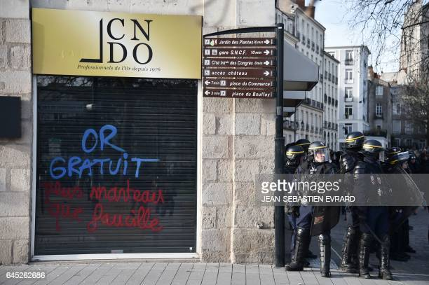 French riot policemen stand guard during clashes with protesters on the edge of a demonstration against the visit of French presidential election...