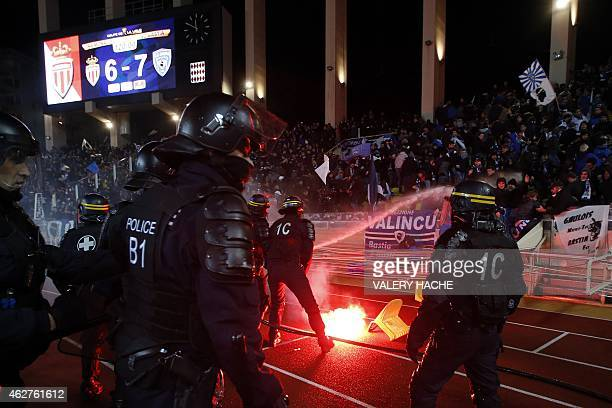 French riot spray water towards Bastia's supporters after they threw chairs and a burning flair on the pitch after Bastia won in penaltyshootouts the...