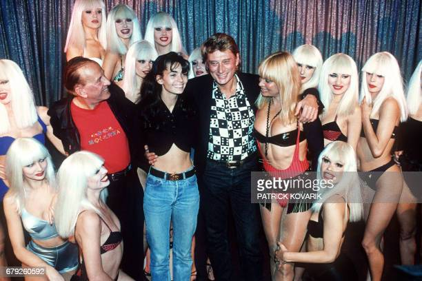 French rock singer Johnny Hallyday and his wife Adeline pose with Crazy Horse Saloon manager Alain Bernardin his wife Lova Moor and dancers during...