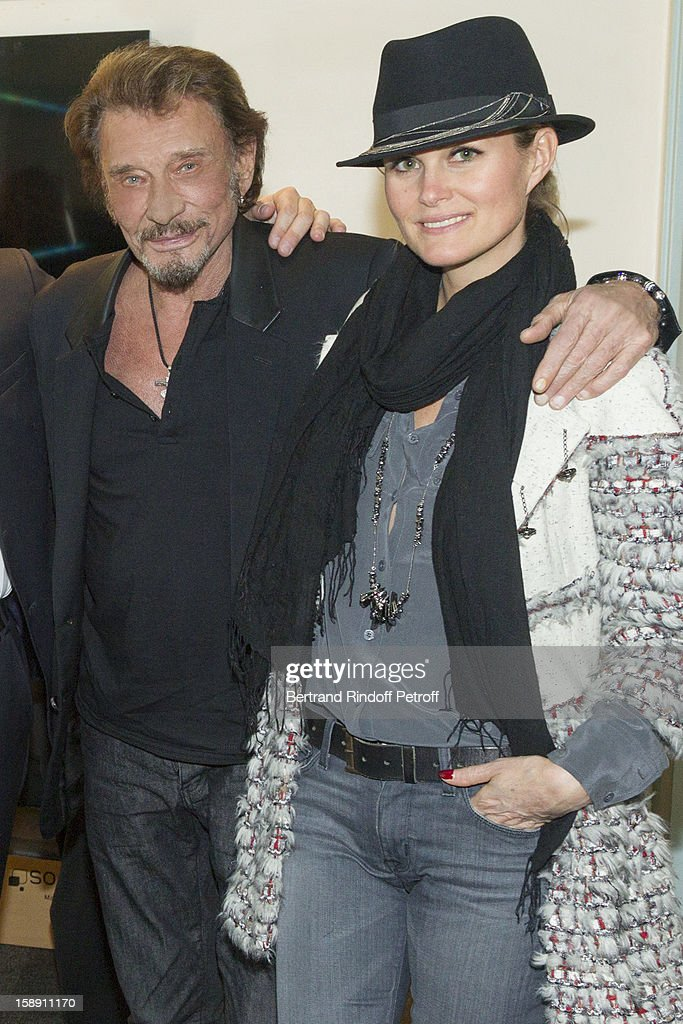 French rocker Johnny Hallyday and his wife Laeticia pose in French impersonator Laurent Gerra's dressing room following his one man show at Olympia hall on December 21, 2012 in Paris, France.