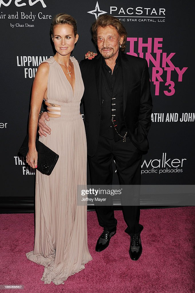 French rocker Johnny Hallyday (R) and Laeticia Hallyday attend The Pink Party 2013 at Barker Hangar on October 19, 2013 in Santa Monica, California.