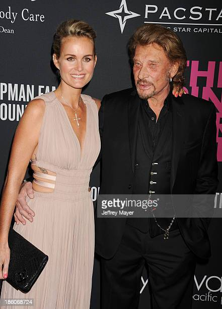 French rocker Johnny Hallyday and Laeticia Hallyday attend The Pink Party 2013 at Barker Hangar on October 19 2013 in Santa Monica California