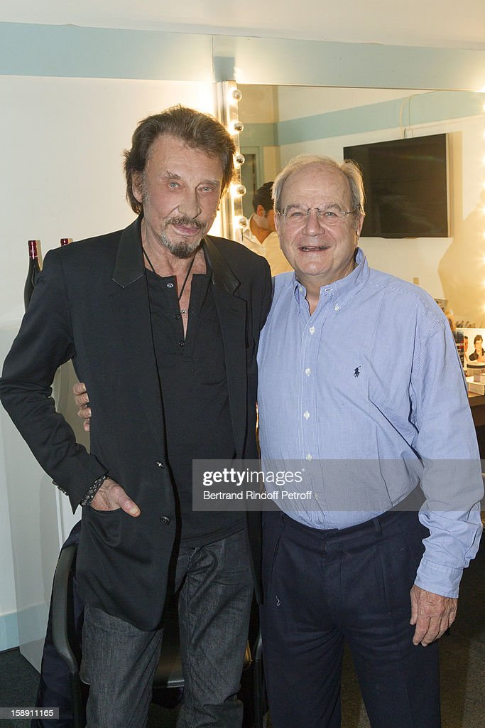 French rocker Johnny Hallyday (L) poses with Marc Ladreit de Lacharierre in French impersonator Laurent Gerra's dressing room following Gerra's one man show at Olympia hall on December 21, 2012 in Paris, France.