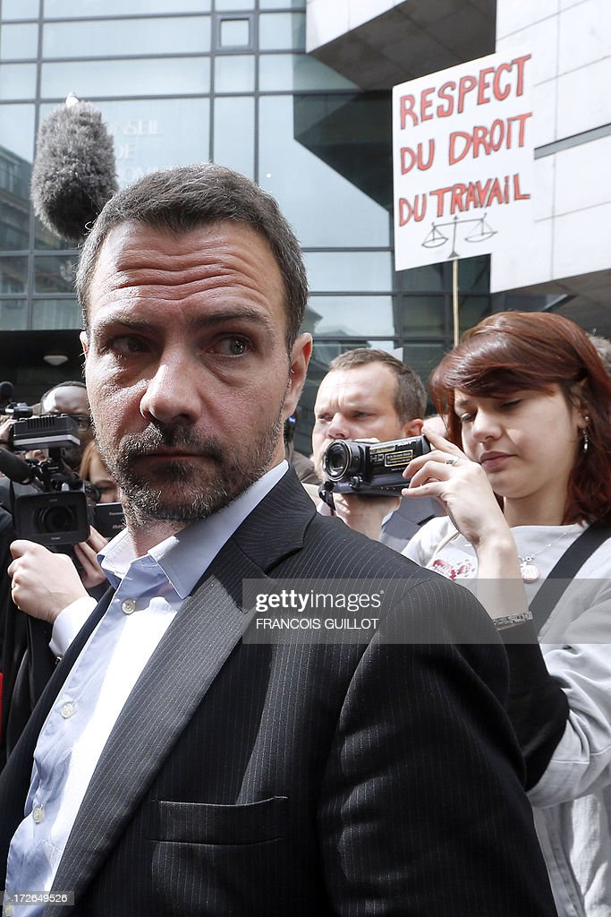 French rogue trader Jerome Kerviel arrives on July 4, 2013 in Paris, at the Prudhommes court (judicial system of relations between workers and employees). Kerviel lost last year his appeal against a three-year jail term and a 4.9-billion-euro fine for his part in France's biggest rogue-trading scandal. The 35-year-old was convicted of forgery and breach of trust for gambling away nearly five billion euros ($6.3-billion) in risky deals as a star trader at Societe Generale, one of Europe's biggest banks. The placard at right reads : 'Respect of labor law'.