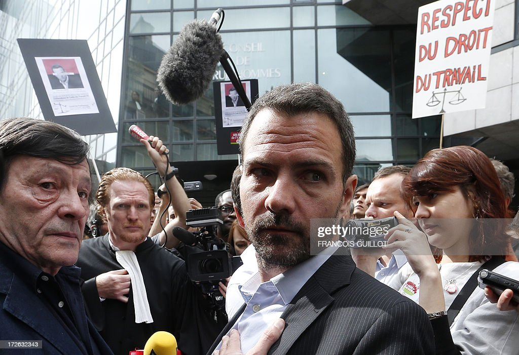 French rogue trader Jerome Kerviel (C) arrives on July 4, 2013 in Paris, flanked by Roland Agret (L), Action Justice association president, at the Prudhommes court (judicial system of relations between workers and employees) flanked by his lawyer David Koubbi ( ). Kerviel lost last year his appeal against a three-year jail term and a 4.9-billion-euro fine for his part in France's biggest rogue-trading scandal. The 35-year-old was convicted of forgery and breach of trust for gambling away nearly five billion euros ($6.3-billion) in risky deals as a star trader at Societe Generale, one of Europe's biggest banks. The placard at right reads : 'Respect of labor law'.