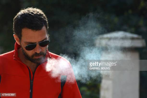 French rogue trader Jerome Kerviel smokes a cigarette prior to leave his hotel in Modena on March 19 during his trek from Rome to Paris 'against the...