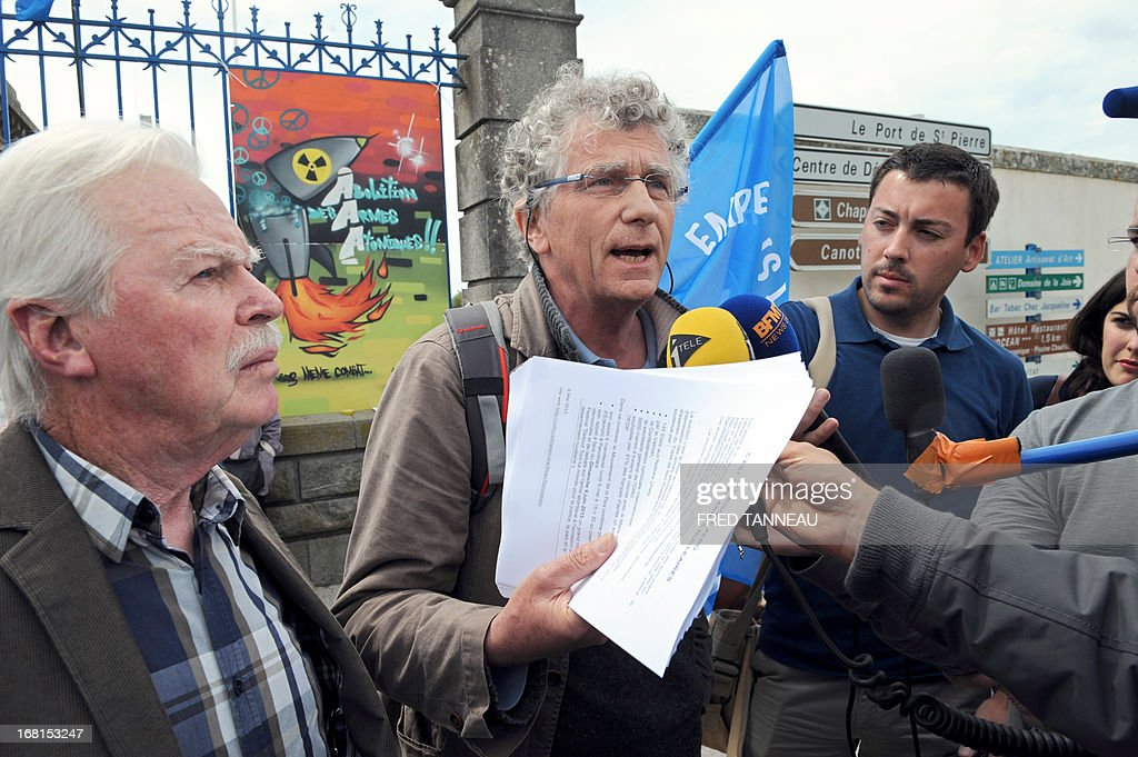 French Roland Nivet (C) in charge of the 'Peace movement' in Brittany, western France, answers to journalists during a protest, on May 6, 2013, in Penmarch a day after a French test of an M51 submarine-launched ballistic missile failed as it self-destructed off the coast of Brittany. The missile was test fired, without a nuclear warhead, from the Vigilant -- a strategic nuclear submarine -- from the Bay of Audierne and had been due to go down in the isolated north Atlantic. At background, the board reads : 'Abolition of nuclear weapons'. TANNEAU
