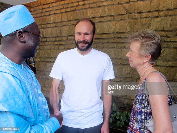 French Roman Catholic priest Georges Vandenbeusch shakes hands on December 31 2013 with Ferdinand Ngoh Ngoh general secretary of the Cameroonian...