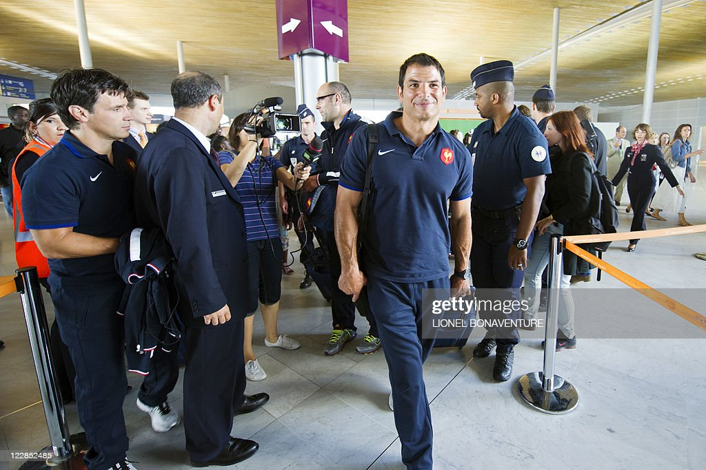 French rugby national team head coach Marc Lievremont (C) and French players arrive at the Roissy airport on August 29, 2011 in Roissy-en-France, northern suburb of Paris, before boarding an airplane to New Zealand to compete in the Rugby Union World Cup. Lievremont talked up his team's chances of winning the World Cup, insisting that their lengthy and intense preparations have given them real hope of lifting the Webb Ellis Trophy.
