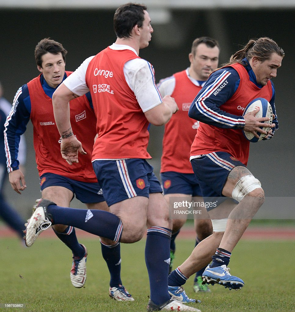 French rugby national team's back row Pierrick Gunther (R) runs with a ball during a training session, on November 20, 2012 in Marcoussis, south of Paris, as part of the team's preparation for the upcoming last test match against Samoa.