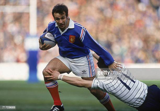 French rugby player Philippe SaintAndre breaks a fingertip challenge from Scot Ken Logan during the Five Nations match at Murrayfield Stadium...