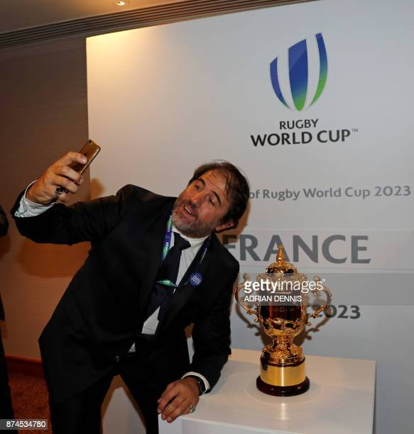 French rugby union federation vicepresident Serge Simon poses for a selfie with the trophy after France was named to host the 2023 Rugby World Cup in...