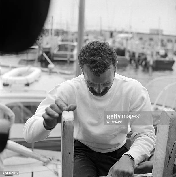 French sailor Eric Tabarly climbs on a ladder at his arrival in Newport Rhode Island on June 18 1964 as he crosses the finish line of the...