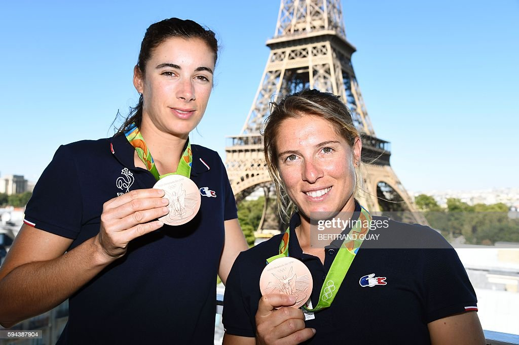 French sailors Helene de France and Camille Lecointre pose with their bronze medals on August 23 in front of the Eiffel tower in Paris France's...
