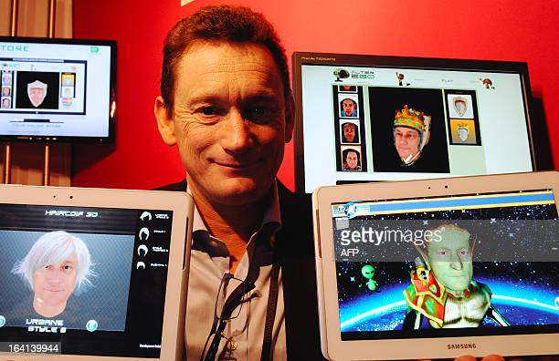 French Sales and Marketing director of Digiteyezer Didier Cholet poses next to computer screens showing various of his avatars made from a scan of...