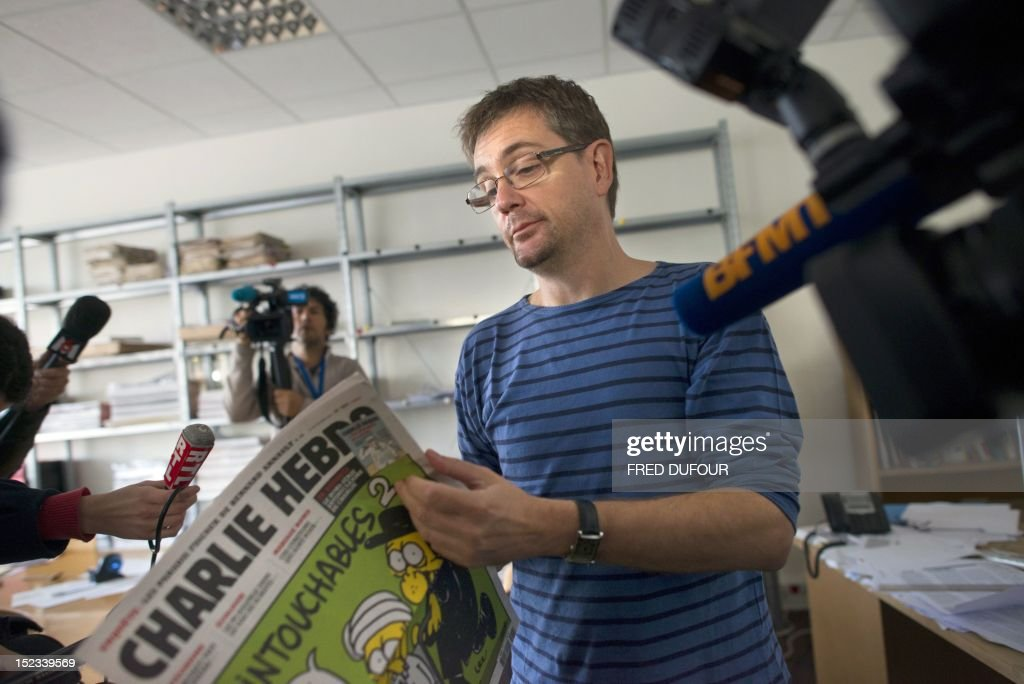 French satirical weekly Charlie Hebdo's publisher, known only as Charb, answers to journalists as he holds, on September 19, 2012 in Paris, at the headquarters, the last issue which features on the front cover a satirical drawing titled 'Intouchables 2'. Inside pages contain several cartoons caricaturing the Prophet Mohammed. The magazine's decision to publish the cartoons came against a background of unrest across the Islamic world over a crude US-made film that mocks Mohammed and portrays Muslims as gratuitously violent. The title refers to 'Intouchables', a 2012 French movie, the most seen French movie abroad, which is selected to represent France for the Oscars nominees, according to one of his directors, Eric Toledano.