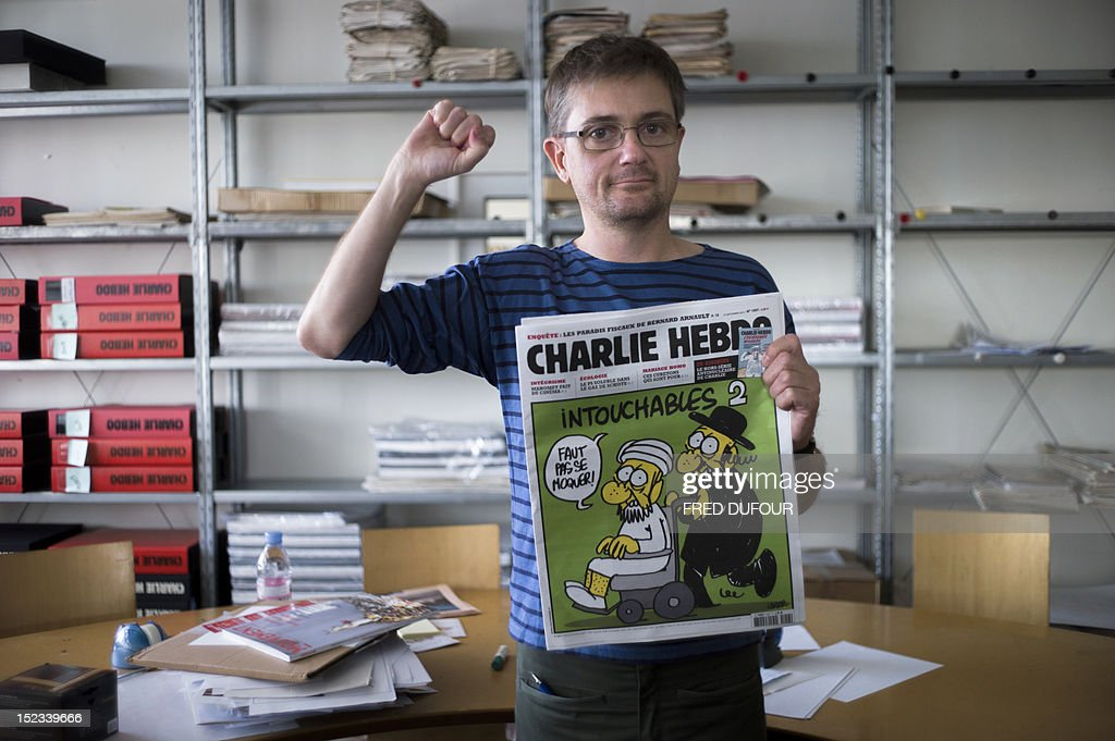 French satirical weekly Charlie Hebdo's publisher, known only as Charb, clenches his fist as he presents to journalists, on September 19, 2012 in Paris, at the headquarters, the last issue which features on the front cover a satirical drawing titled 'Intouchables 2'. Inside pages contain several cartoons caricaturing the Prophet Mohammed. The magazine's decision to publish the cartoons came against a background of unrest across the Islamic world over a crude US-made film that mocks Mohammed and portrays Muslims as gratuitously violent. The title refers to 'Intouchables', a 2012 French movie, the most seen French movie abroad, which is selected to represent France for the Oscars nominees, according to one of his directors, Eric Toledano.