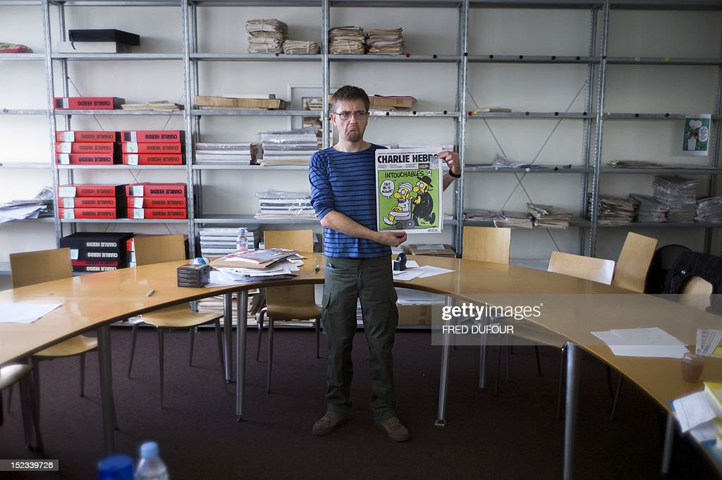 French satirical weekly Charlie Hebdo's publisher, known only as Charb, grimaces as he presents to journalists, on September 19, 2012 in Paris, at the headquarters, the last issue which features on the front cover a satirical drawing titled 'Intouchables 2'. Inside pages contain several cartoons caricaturing the Prophet Mohammed. The magazine's decision to publish the cartoons came against a background of unrest across the Islamic world over a crude US-made film that mocks Mohammed and portrays Muslims as gratuitously violent. The title refers to 'Intouchables', a 2012 French movie, the most seen French movie abroad, which is selected to represent France for the Oscars nominees, according to one of his directors, Eric Toledano.