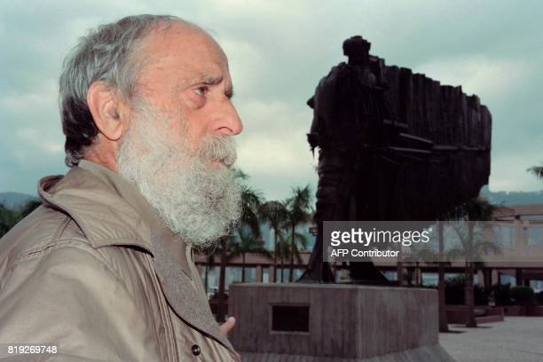 French sculptor Cesar poses in front of his work 'The Flying Frenchman' on January 7 1993 for the first time since it was erected on Hong Kong's...