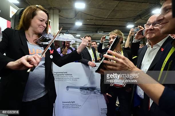 French Secretary of State Axelle Lemaire tries out the 3Dvarius electric violin based on a real Stradivarius violin while visiting French tech booths...