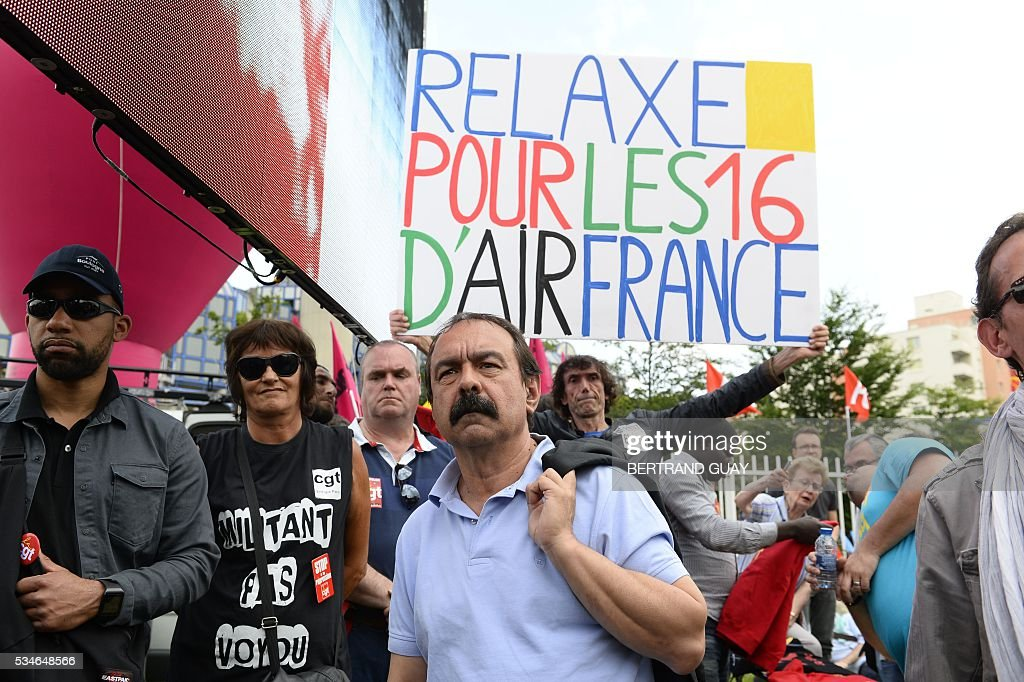 French secretary-general of the General Confederation of Labour (CGT) worker's union, Philippe Martinez poses outside the court of Bobigny, northern Paris on May 27, 2016 as the trial of 15 French CGT union's members judged for the episode of the torn shirt was referred to September, in full showdown initiated by the union with the government on labor law. On October 5, 2015 under the cries of naked, naked and resignation , the Air France human resources director found himself shirtless, tattered shirt during a protest after the announcement of a restructuring of the airline threatening nearly 3,000 jobs. The banner reads ' 'acquittal for the 16 of Air France'.