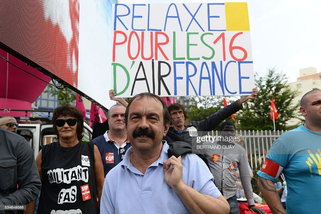 French secretary-general of the General Confederation of Labour (CGT) worker's union, Philippe Martinez stands outside the court of Bobigny, northern Paris on May 27, 2016 as the trial of 15 French CGT union's members judged for the episode of the torn shirt was referred to September, in full showdown initiated by the union with the government on labor law. On October 5, 2015 under the cries of naked, naked and resignation , the Air France human resources director found himself shirtless, tattered shirt during a protest after the announcement of a restructuring of the airline threatening nearly 3,000 jobs. The banner reads ' 'acquittal for the 16 of Air France'.